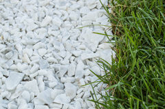 Background track from white stones, near green grass lawn Royalty Free Stock Images