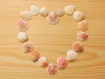 Background travel vacation. Heart of seashells. Heart of seashells on a wooden background. Conceptual symbol Royalty Free Stock Photos