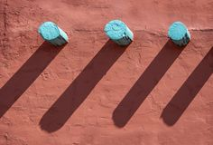 Background - Turquoise corbels and their long shadows on an orange stucco wall on southwestern style building.  royalty free stock images