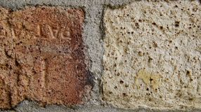 Very Old Brick Background. Background of two half bricks, one with orange and brown the other is beige with small brown dots. Horizontal. Two different colored Royalty Free Stock Photo
