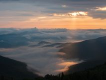 Background of Ukrainian mountains at summer. Sunset in west Ukraine. Carpathians mountains in august. Sun beams. Illuminating the clouds flowing between high stock image