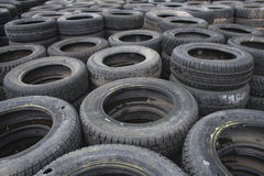 Background of used car tires. Stacks of used or worn car tires receding into distance Stock Images