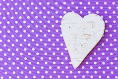 Valentines or Mothers Day background with heart on vintage fabric. Background for Valentine or Mothers day card with white heart on purple dotted fabric and copy royalty free stock images