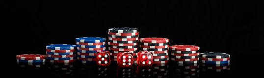 Background vertical rows of different poker chips and red dice stand on a black background long photo stock image