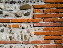 Background of a wall of brick and stone cemented with concret. stock photo