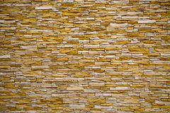 The background of the wall, lined with artificThe background of the wall, lined ial stone irregular rectangular white and yellow. royalty free stock photography