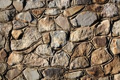 Background - Stacked Stone Wall. Background - a wall made of natural stone of different sizes in a sunny day Stock Photography