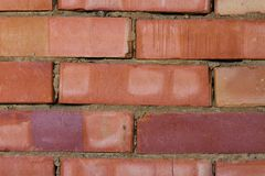 Background, a wall made of red bricks. Partially crumbled. Bricks of different colours Royalty Free Stock Photography
