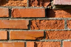 Background, a wall made of red bricks, partially crumbled. Old building Royalty Free Stock Photos