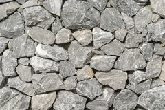 Background, a wall of rough broken gray stones, holding on a clay cement Foundation stock photos