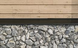 Wall of rough broken grey stones and wooden planks stock images