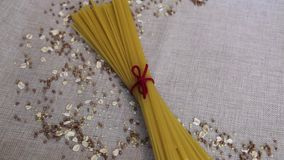Background wallpaper, pasta spaghetti, croup, buckwheat, rice, oatmeal, cereal, scattered on fabric stock footage