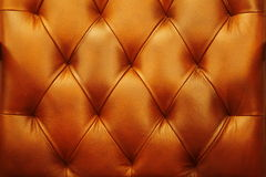 The background is a warm dark orange upholstery leather furniture, door. Seamless leather texture. The seamless orange leather texture.  Luxury  leather close Stock Photography