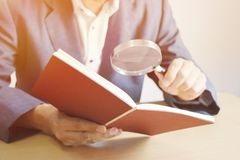 Background in warm light, Elderly man business man holding book. Use a magnifying glass to read the text. royalty free stock image