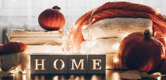 Background with warm sweaters and the inscription HOME. Pile of knitted clothes with leaves, pumpkins. Coziness. Autumn concept. Background with warm sweaters royalty free stock photography