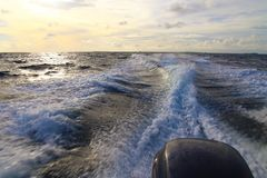 Background water surface behind of fast moving motor boat. Sunlight falls on the water Stock Photography