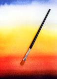 Background of watercolour wash with brush. Having fun in art class - An image of a paintbrush on an abstract and colorful backgrounds of watercolor washed stock image