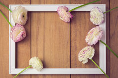 Background for wedding or party invitation. Picture frame with flowers on wooden table. View from above Royalty Free Stock Images