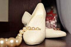 Background Wedding ring on the bride's shoes. Background Wedding gold rings on the bride's shoes Royalty Free Stock Images