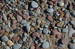 Background of wet pebbles and sand. Background of smooth and wet pebbles and sand at a beach Stock Images
