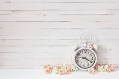 Background with white alarm clock and small pink roses on white Stock Photography