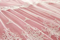 Background of white delicate lace fabric over pink background. Background of white delicate lace fabric over pink background Royalty Free Stock Image