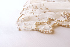 Background of white delicate lace fabric and pearls. Royalty Free Stock Photos