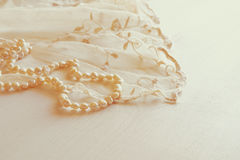 Background of white delicate lace fabric and pearls. Stock Image