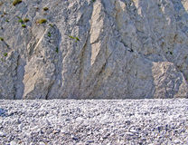Background with white pebbles on the beach and a rocky wall Stock Photo
