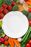 Background white plate and organic vegetables, vertical top view Royalty Free Stock Image