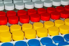 Background of white, red, yellow and blue cans stock photo