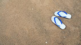 Background of white slippers or flip flops on beach. The concept of relaxing time Royalty Free Stock Photo