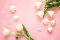 Background with white tulips and meringue cookies on pink. Copy Royalty Free Stock Photos