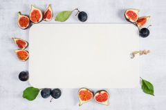 Background with white wooden cutting board decorated with figs and plums stock photos