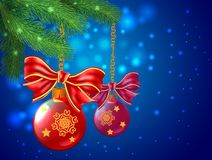 Background wiht Christmas balls and bows are hanging a branch tr. Ee on blue Royalty Free Stock Image