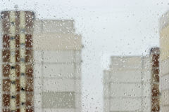 Background of the window pane during a rain. Background of the window pane with the streams and drops of water and blurred apartment buildings through the glass Stock Image