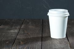 White paper cup.jpg. Background of a wooden countertop with a white paper cup for coffee to go Stock Photography
