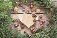 Background with wooden heart, pine branches, nuts, cinnamon stic Stock Photography