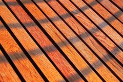 Background of wooden planks decor. Evening sunlight and shadows on wooden texture. Cherry wood texture light background. Background of wooden planks decor Stock Photos