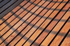 Background of wooden planks. Evening sunlight and shadows on wooden texture. Cherry wood texture light background. Background of wooden planks. Evening sunlight Stock Image