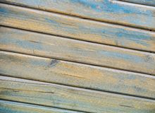 Background of wooden slats of planks located on a diagonal of yellow and blue color aged wood stock photo