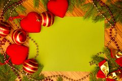 On the wooden surface of the branches of spruce and Christmas toys in the shape of a heart stock image