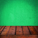 Background with wooden table and grunge green wall Royalty Free Stock Image
