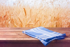 Background with wooden table and wheat field Royalty Free Stock Images