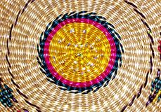 Background is a woven spiral colored circle made of straw. Royalty Free Stock Image