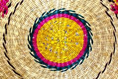 Background is a woven spiral colored circle made of straw. Royalty Free Stock Images