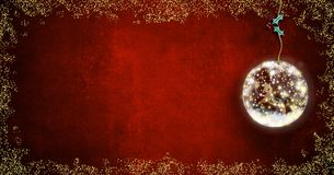 Background for writing christmas cards. Rocking horse old toy  inside xmax ball on red background with space for message, panoramic format Royalty Free Stock Photo