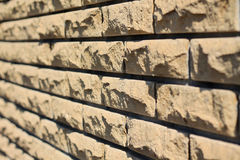Background of yellow facing bricks. Side view close up. Stock Images