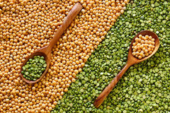 Background of yellow and green dried peas and two wooden spoons. Yellow and green dried peas and two wooden spoons.view from above Royalty Free Stock Images