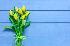 Background with yellow tulips on blue painted wooden planks. Place for text. Top view with copy space Royalty Free Stock Images